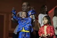 Zilong Zheng (left) cheers with his son Tianxing Zheng (center) and his daughter Tianle Zheng (right) after participating in an onstage game during a Chinese New Years celebration in Baker University Center in Athens, Ohio, on Jan. 29, 2017.  Zheng and his children were among a group of people to volunteer to come up from the crowd and play a Chinese game similar to hacky sack during the celebration's intermission. (FILE)