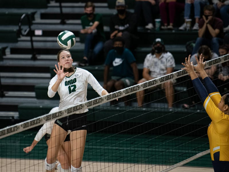 Bobcats Middle Blocker Caitlin O' Farrell (12) midair tries to push the ball over the net at a  game against Toledo Rockets  held at Ohio University in Athens,Ohio on Sept. 25, 2021. The rockets win 3-0