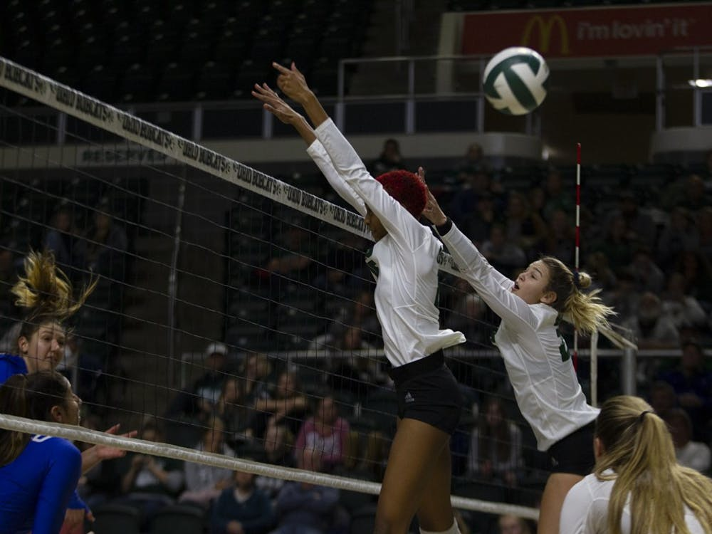 Tia Jimerson (15) and Maggie Nedoma go up for a block in a match against Buffalo in the Convocation Center on Friday, November 15, 2019. (Jesse Jarrold-Grapes | For The Post)