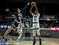 Ohio's Erica Johnson (#4) attempts a shot with pressure from Kent's Katie Shumate (#14) during the home game on Saturday, Feb. 8, 2020. The bobcats won 63-57.