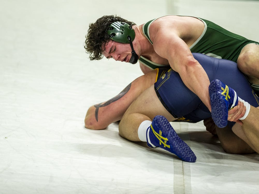 Ohio University redshirt sophomore Jordan Ernest works to take down Kent State's Jacob Cover during the home match on Sunday, Feb. 7, 2021 in Athens, Ohio.