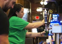 Breonna Stanley, a bartender at Pigskin Bar and Grille, pours a cup of green beer during Green Beer Day on March 7, 2018. (FILE)
