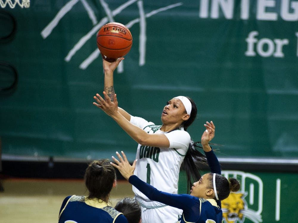Ohio guard Cece Hooks (1) takes the ball to the basket with pressure from a University of Akron defender during the home game on Saturday, Jan. 30, 2021, in Athens, Ohio.
