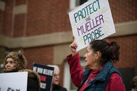 Mary Hogan, from Guysville, Ohio, waves a protest sign at the Save the Mueller Investigation protest outside the Athens County Courthouse on Nov. 8.