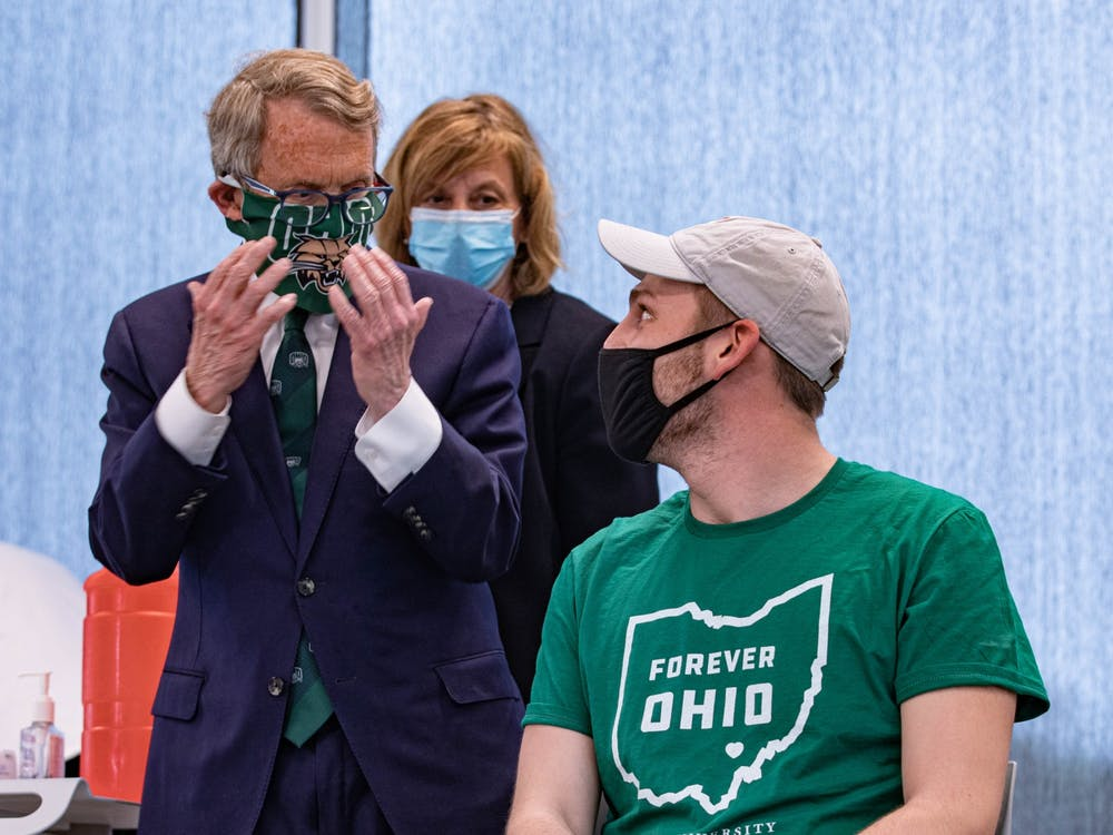 Ohio Gov. Mike DeWine talks about wearing masks with Prestin Minter at a public relations event hosted at Ohio University's Heritage College of Osteopathic Medicine in Athens, Ohio, on Monday, April 12, 2021.