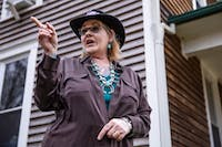 Kruzel stands outside her home and points to her surrounding neighbors in Rutland, Ohio, where she hosts many of her clients to come for appointments, readings, and guidance.