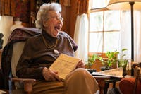 Marjorie Stone laughs while holding her book, Getting to Know Athens County, in her home on Wednesday, April 3, 2019.