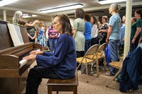 Nancy Pierce plays the piano as the Calliope Feminist Choir sings along on Monday.