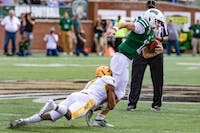 Ohio's QB Nathan Rourke (12) runs with the ball as Kent State's CB Jamal Parker Jr. (7) grabs Rourke by the legs for a tackle in a game held at Peden Stadium on Saturday, Oct. 19, 2019.