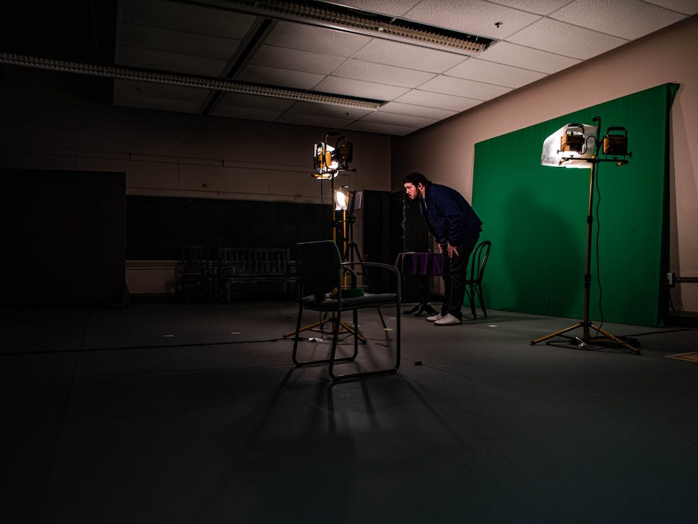 Aaron Gates, an Ohio University fourth-year working toward his BFA in acting, sets up a tablet with a green screen in preparation for his zoom call as part of a rehearsal for Tantrum Theater on Wednesday, Oct. 21, 2020.