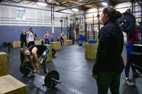 Haley Billett (right) provides guidance to a student in her CrossFit class held at CrossFit SEO on Monday, Jan. 13.