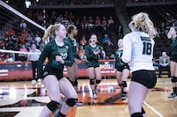 The OU volleyball team rallies to celebrate a point scored during their game against BGSU on Saturday.