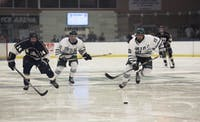 Ohio University's Jacob Houston (middle) and Jake Faiella (right) go against John Carroll's John McMahon (left) for the puck at Ohio University's Bird Arena on Saturday, Sept. 23, 2017. (FILE)
