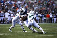 Kylan Nelson (No.23) goes to make a tackle on Olamide Zaccheaus during the Ohio vs Virginia football game.
