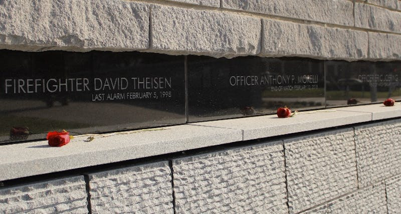 The names of firefighter David Theisen and Officers Anthony Morelli and Eric Joering are engraved in the new stone memorial wall above a water feature.