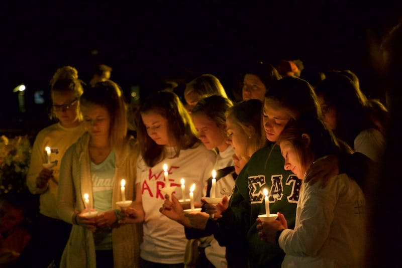 Students attend vigil for fellow student Anna Phillips, illuminated by candlelight.