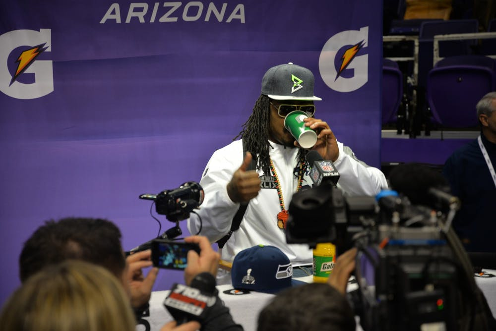 """<p>Marshawn Lynch in a 2015 press conference</p> <h6>Photo Credit: Jeremy Vandroff - WEBN-TV / <a href=""""https://www.flickr.com/photos/politicalpulse/16383989285"""" target=""""_self"""">Flickr</a></h6>"""