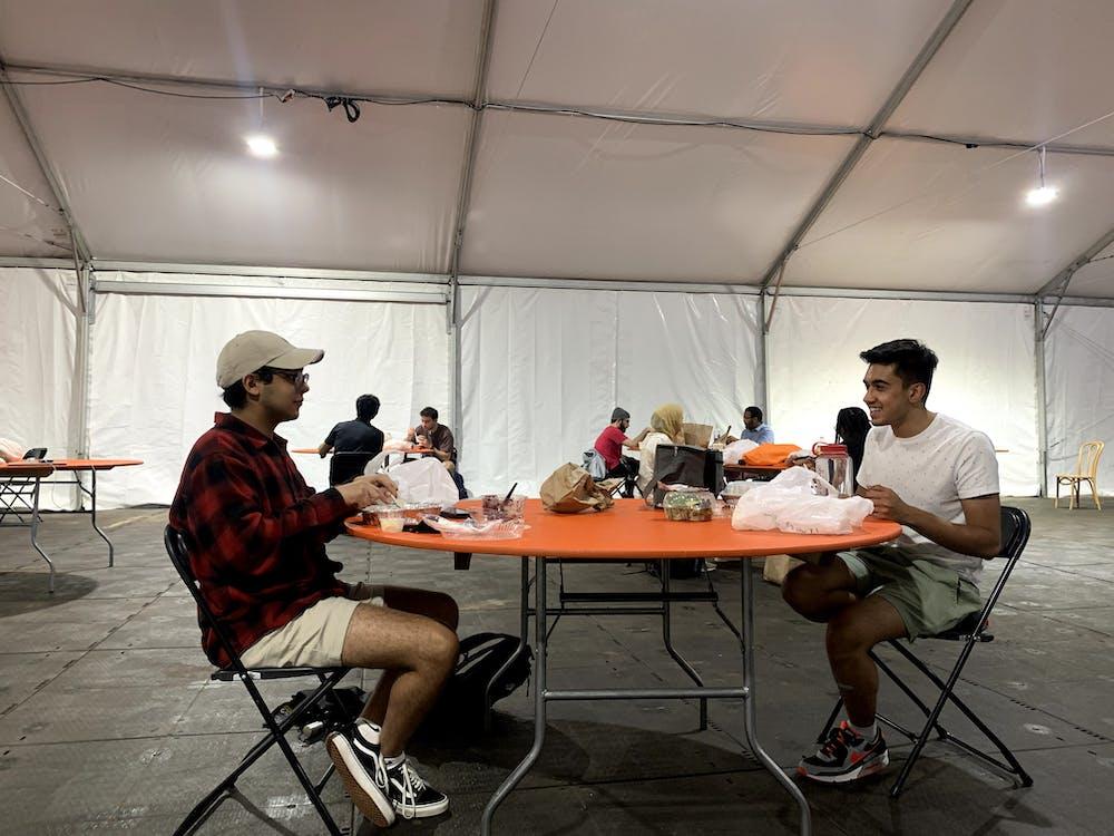 <h5>Jad Bendarkawi '24 (l.) and Faraz Awan '24 enjoy Iftar together in the Frist South Lawn tent.</h5> <h6>Courtesy of Fawaz Ahmad '22.</h6>