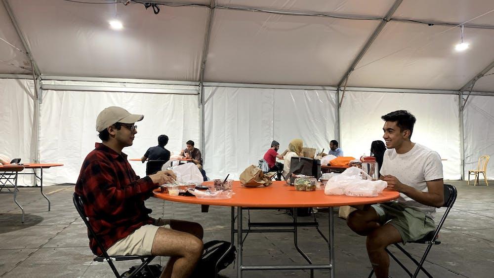 Jad Bendarkawi '24 (l.) and Faraz Awan '24 enjoy Iftar together in the Frist South Lawn tent. Courtesy of Fawaz Ahmad '22.