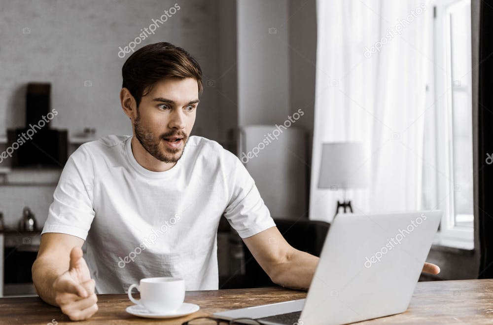 """<p>""""Surprised young man with coffee using laptop at home"""" by AllaSerebrina / <a href=""""https://depositphotos.com/227381938/stock-photo-surprised-young-man-coffee-using.html"""" target=""""_self"""">DepositPhotos</a></p>"""