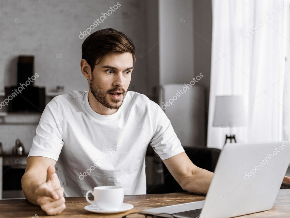 """""""Surprised young man with coffee using laptop at home"""" by AllaSerebrina / DepositPhotos"""