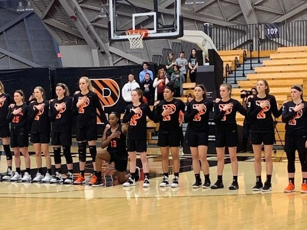 Sydney Jordan kneels with her hand over her heart during the National Anthem before Princeton's Senior Night game against Harvard. Photo: Josephine de La Bruyere / The Daily Princetonian
