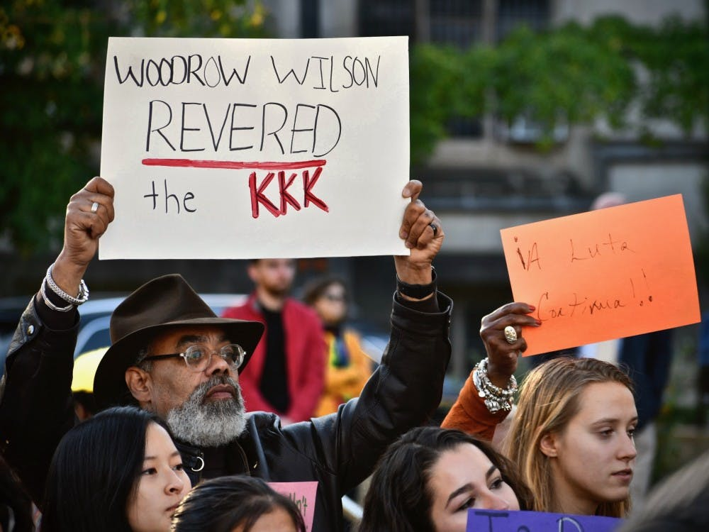 People hold signs denouncing Woodrow Wilson's white supremacy. Photo Credit: Jon Ort / The Daily Princetonian