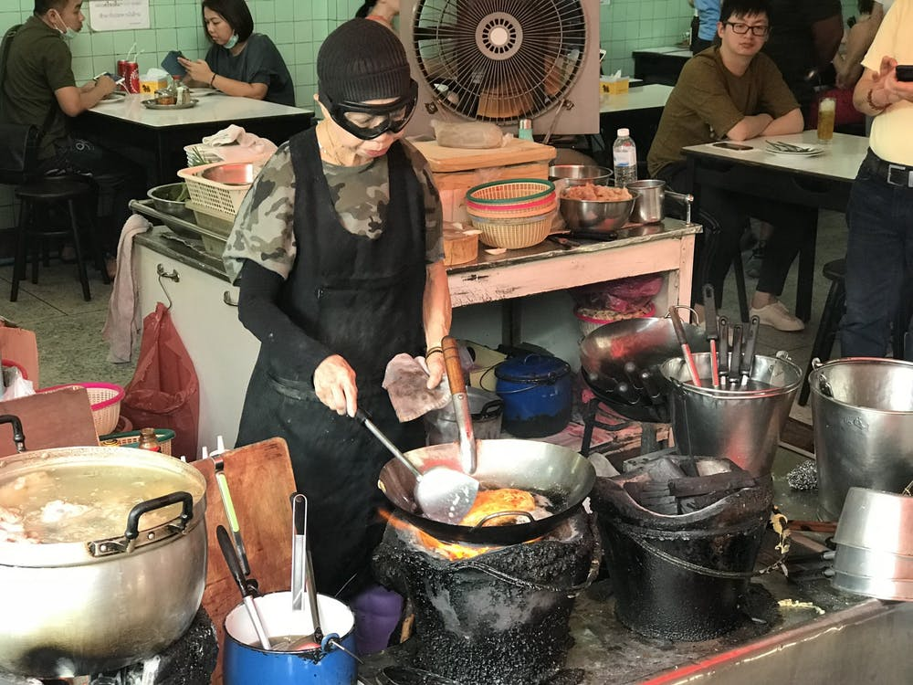 "Jay Fai, the star of Street Food: Asia's Bangkok episode, cooks one of her famous crab omelets. ""Jay Fai, bangkok 20180406 cooking crab omelette on coal"" by Sais.isa / CC BY-SA"