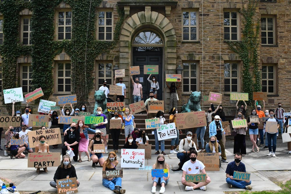 <h5>Students hold cardboard signs with hand-painted slogans urging fossil fuel divestment at the April 24 rally.</h5> <h6>Mark Dodici / The Daily Princetonian</h6>