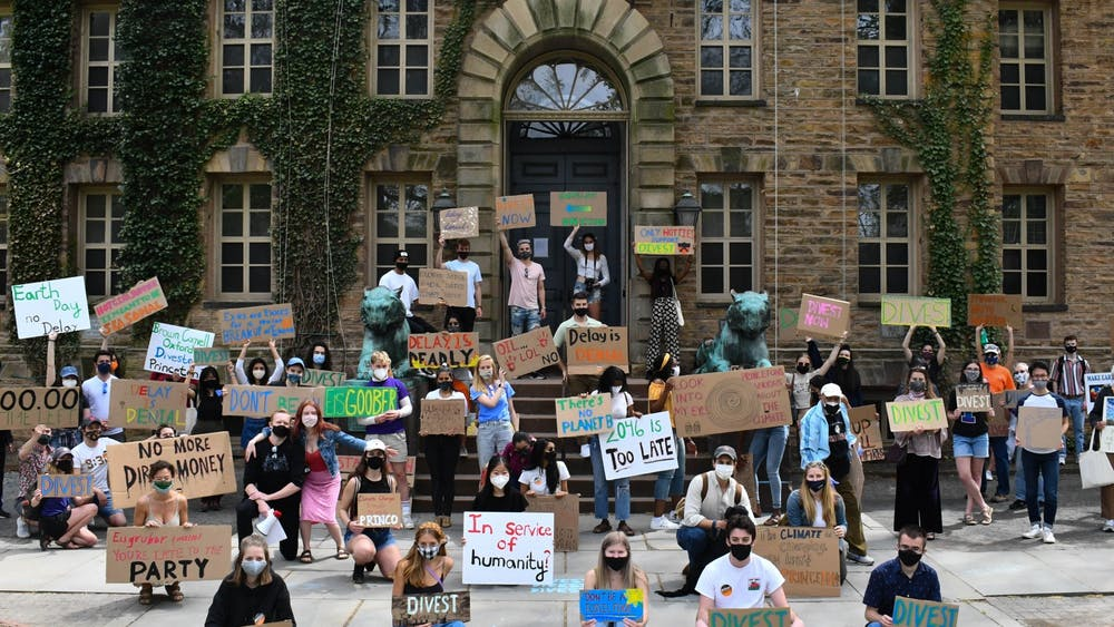 Students hold cardboard signs with hand-painted slogans urging fossil fuel divestment at the April 24 rally. Mark Dodici / The Daily Princetonian