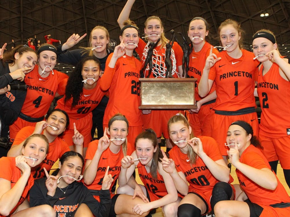 Women's basketball team celebrates their Yale win with trophy and pieces of the net. Photo courtesy of Beverly Schaefer / GoPrincetonTigers.com