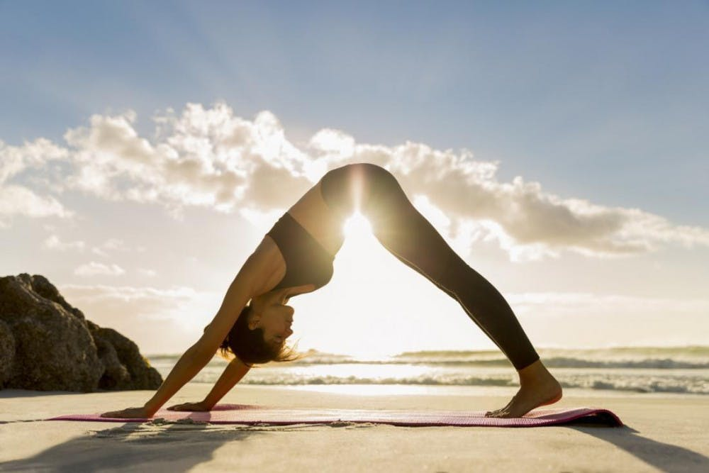 a-woman-practicing-yoga-on-the-beach