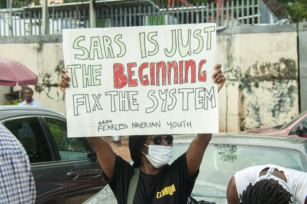 """<h5>A protestor holds a sign that reads, """"SARS IS JUST THE BEGINNING ... FIX THE SYSTEM,"""" signed by """"Fearless Nigerian Youth.""""</h5> <h6>Opara God's-Promise Chukwudiebube for The Daily Princetonian</h6>"""