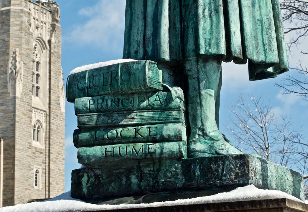 <p>A stack of books beneath the feet of the John Witherspoon statue near Firestone Library. A recently-circulated list of anti-racist demands signed by over 350 faculty members calls for the statue's removal.&nbsp;</p> <h6>Photo courtesy of © Richard Trenner '70</h6>