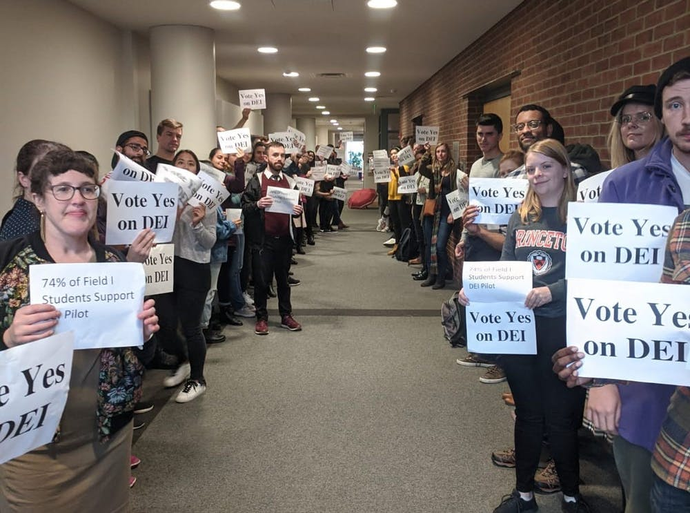 """<h6>Graduate students hold signs reading """"Vote Yes on DEI"""" in February.</h6> <h6>Photo courtesy of Aaron Charlop-Powers</h6>"""