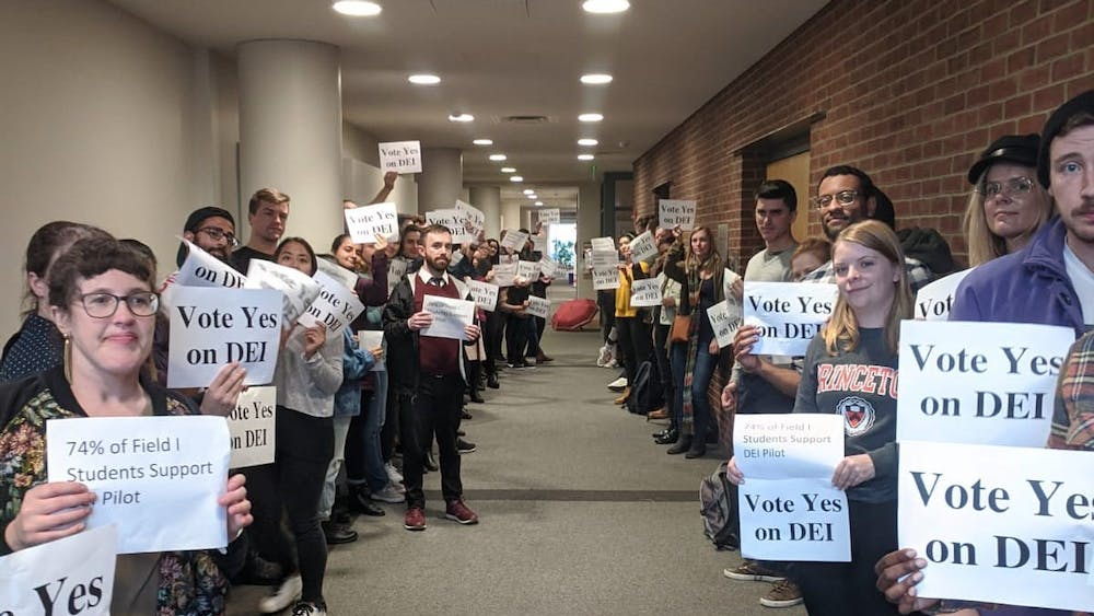 """Graduate students hold signs reading """"Vote Yes on DEI"""" in February. Photo courtesy of Aaron Charlop-Powers"""