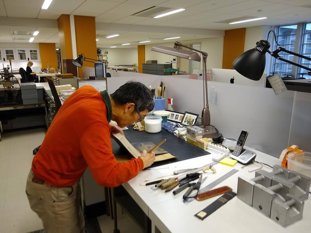 <p>Conservation Technician II Man Liu restores a book's spine.&nbsp;</p> <h6>Photo Credit: James Anderson / The Daily Princetonian&nbsp;</h6>