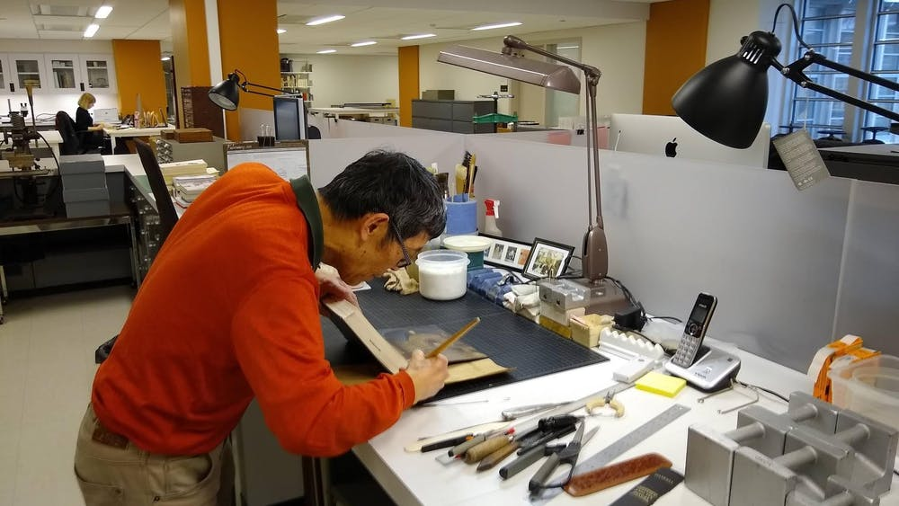 Conservation Technician II Man Liu restores a book's spine.  Photo Credit: James Anderson / The Daily Princetonian