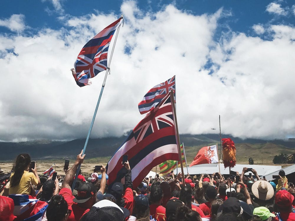 """2019 – Kia'i (protectors) wave inverted Hawaiian flags to illustrate a nation in distress; their hands, which are in a """"triangle shape"""" to indicate a shape of a mountain, highlight their support and love for the Hawaiian people's sacred Mauna Kea during the Thirty-Meter Telescope (TMT) protests. Photo Courtesy of Monet Bisch"""