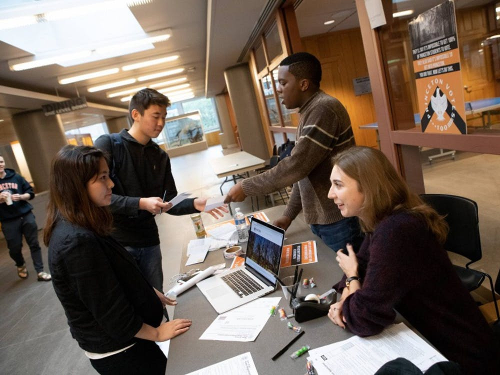 Jonathan Haynes (back right) and Amanda Morrison (front right) talk with first-year Allen Dai (back left) and junior Eun Ahn (front left) about the Vote100 Initiative.  Courtesy of Office of Communications