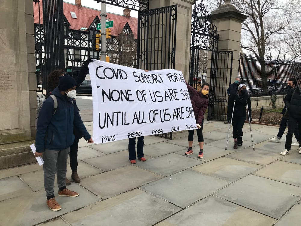 """<h5>Demonstrators unfurl a banner reading """"COVID SUPPORT FOR ALL / 'NONE OF US ARE SAFE UNTIL ALL OF US ARE SAFE.'""""</h5> <h6>Isabella Shutt / The Daily Princetonian</h6>"""
