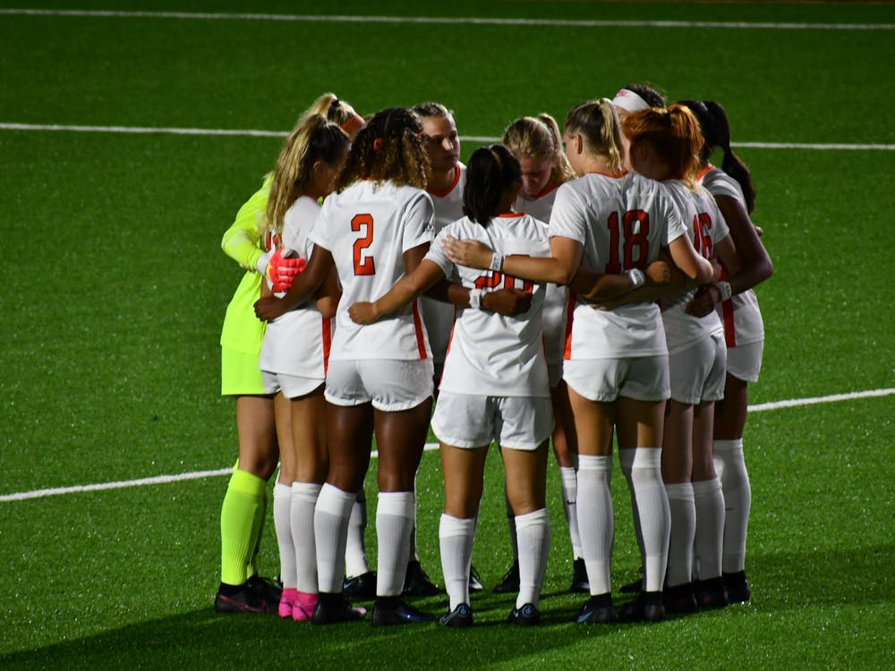 The women's soccer team meets in a quick circle before starting the second half of their game against Yale Saturday night. The score was still 0–0 at this point. Natalia Maidique / The Daily Princetonian