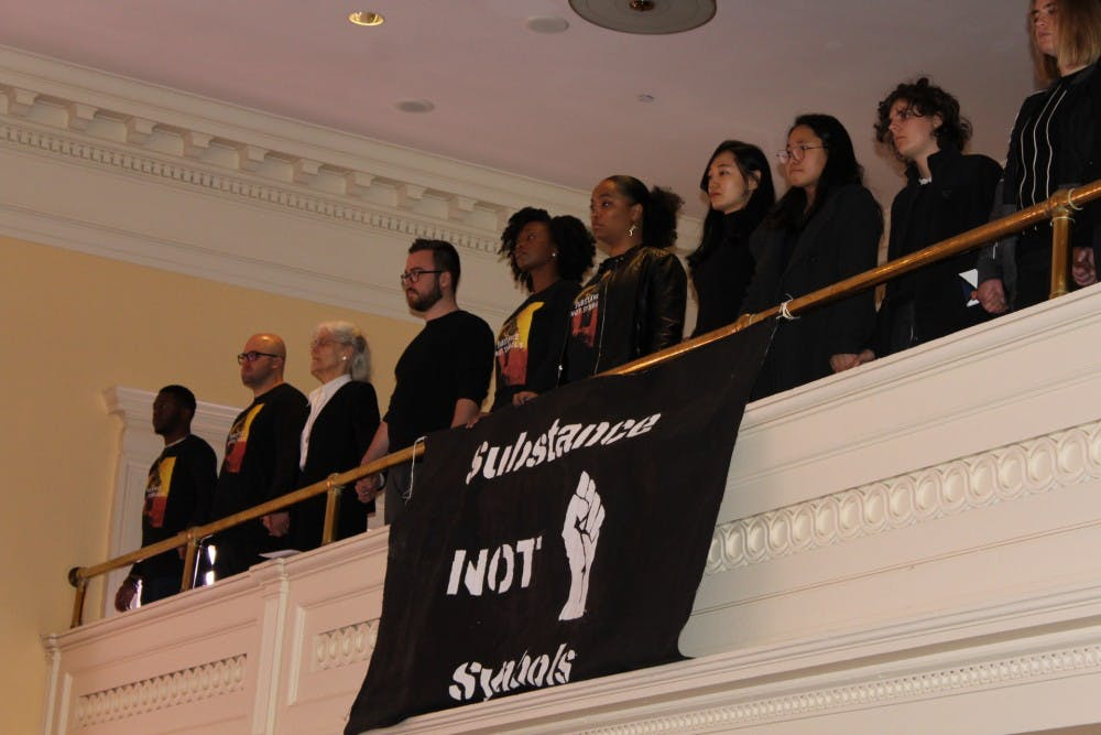 <h6>A group of seminarians stand behind a reparations protest banner.</h6> <h6>Courtesy of Archange Antoine</h6>
