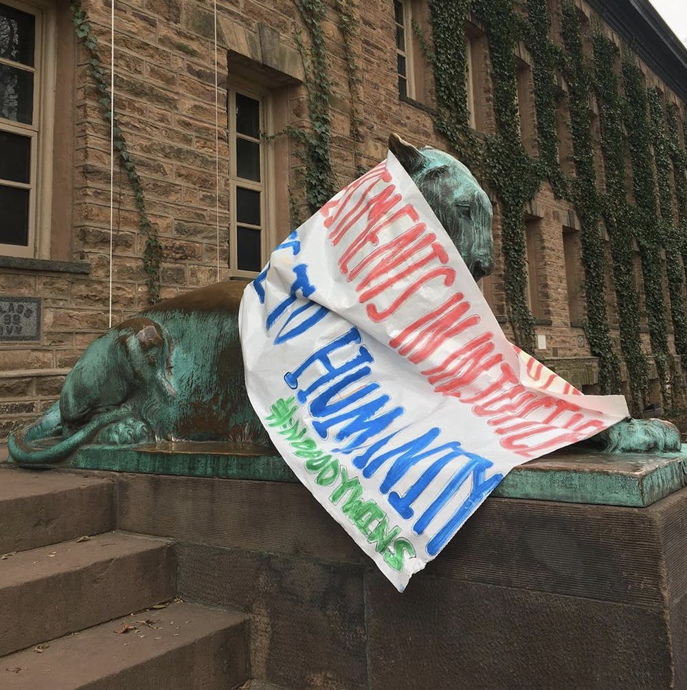 <h5>A banner from Divest Princeton's Feb. 13, 2020 protest draped on a tiger sculpture outside of Nassau Hall.</h5> <h6>Courtesy of Anna Hiltner '23</h6>