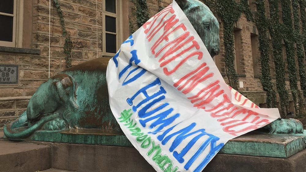 A banner from Divest Princeton's Feb. 13, 2020 protest draped on a tiger sculpture outside of Nassau Hall. Courtesy of Anna Hiltner '23