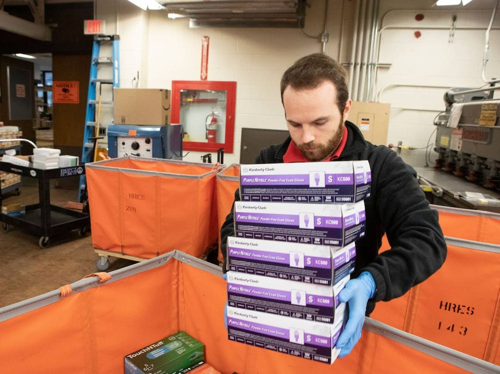 <p>Sean Farrell, senior workplace safety specialist in Environmental Health and Safety, sorts through boxes of personal protective equipment.</p> <h6>Denise Applewhite / University Office of Communications</h6>
