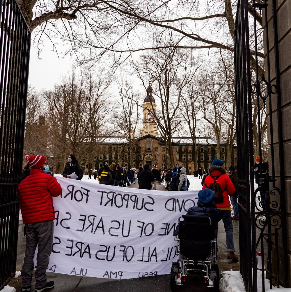 <h5>Protestors hold up a sign in front of Nassau Hall.&nbsp;</h5> <h6>Candace Do / The Daily Princetonian</h6>