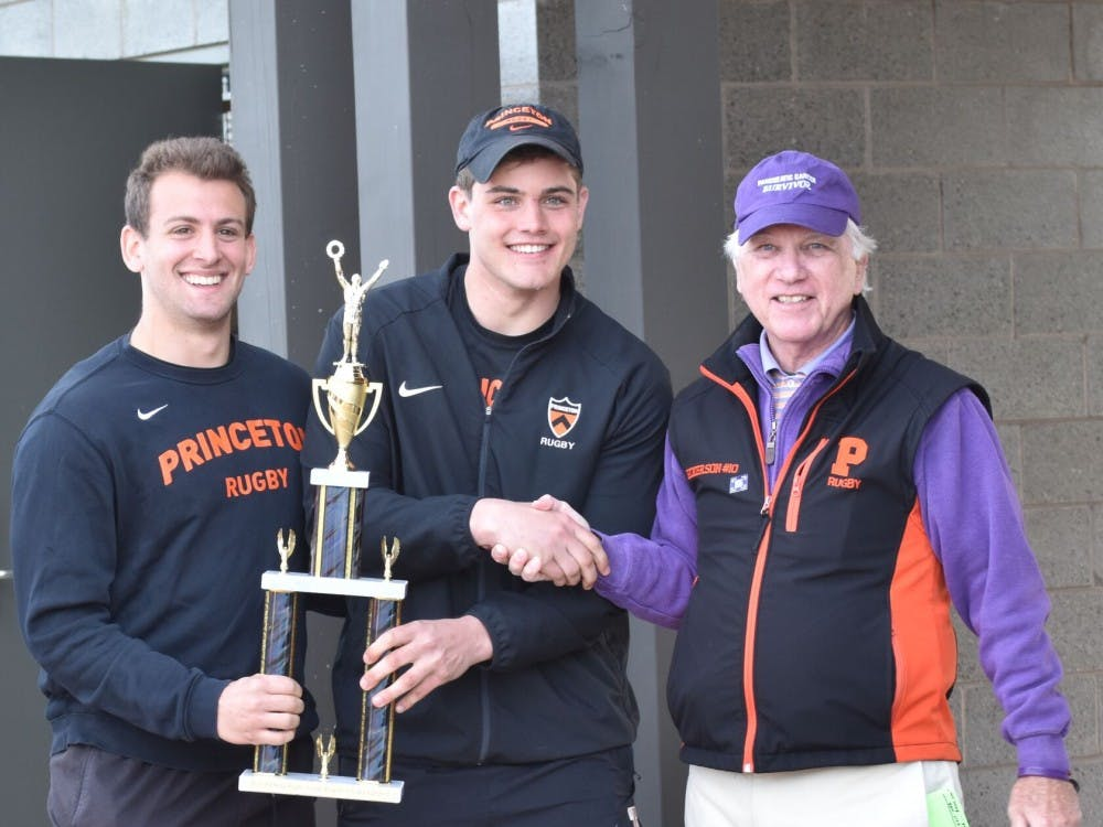 Senior captains Mark Goldstein (left) and Billy Haynes (middle) pose with Stuart Rickerson '71 (right) following the Tigers' Rickerson Cup Victory