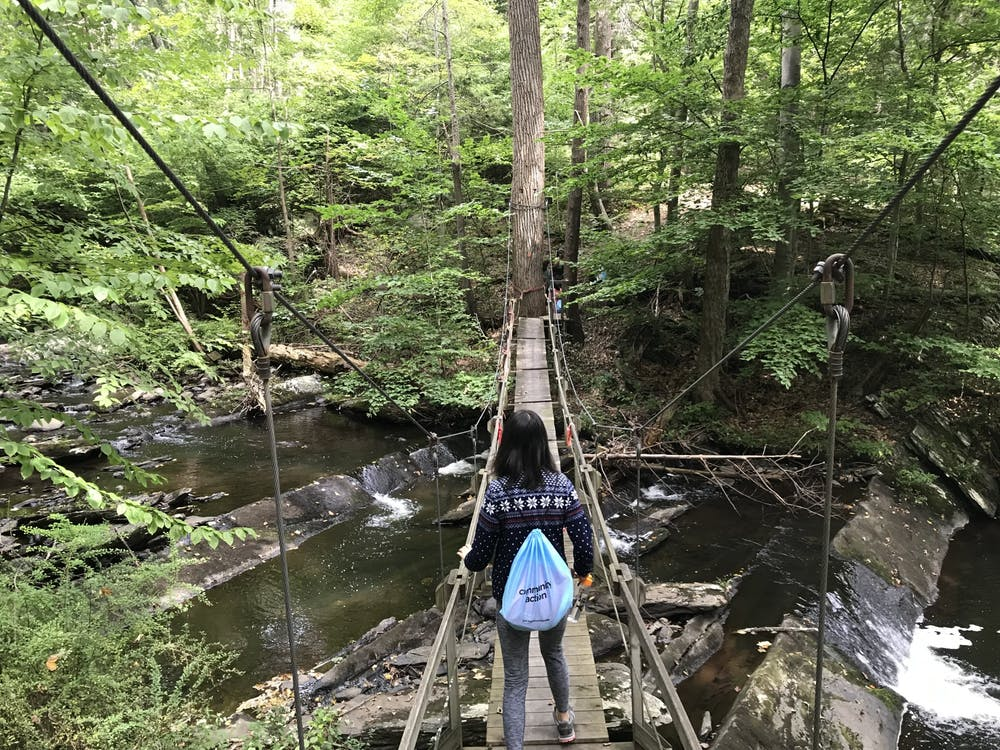 A member of the Class of 2023 walks across a bridge at the Princeton-Blairstown Center as part of their Community Action trip. Photo Credit: Zachary Shevin / The Daily Princetonian