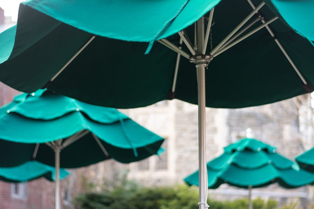 <h5>Umbrellas recently erected outside the WuCox Dining Hall offer a shady place to study or eat.</h5> <h6>Julian Gottfried / The Daily Princetonian</h6>